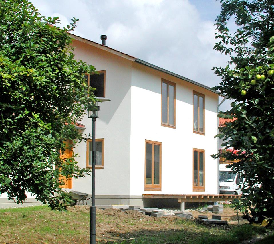 Fassadenbündige Eichenfenster führen auf die Holzterrasse